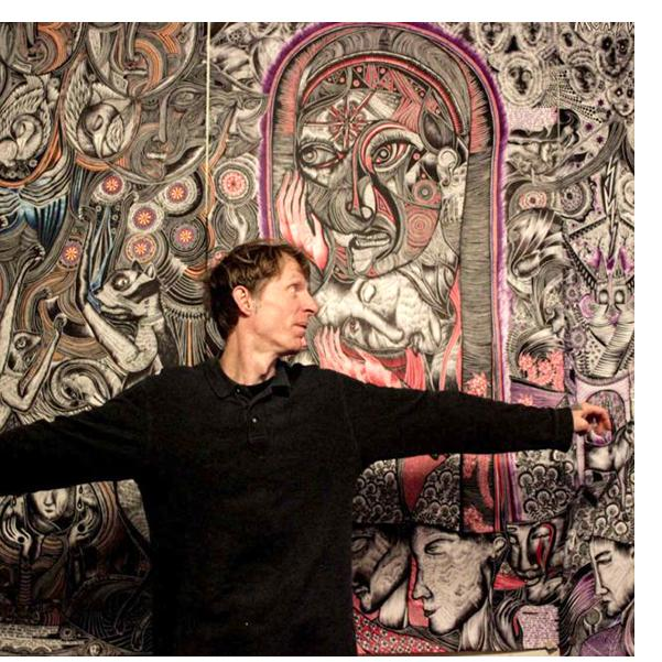 """Justin in front of three panels of his """"cycloramic story scroll,"""" 2020. Photo by Mandy Katz."""